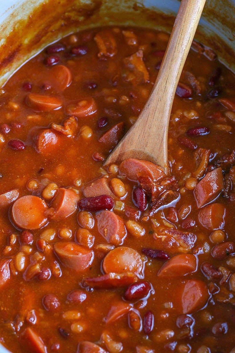 Franks and beans in a crockpot with a wooden spoon scooping some up.