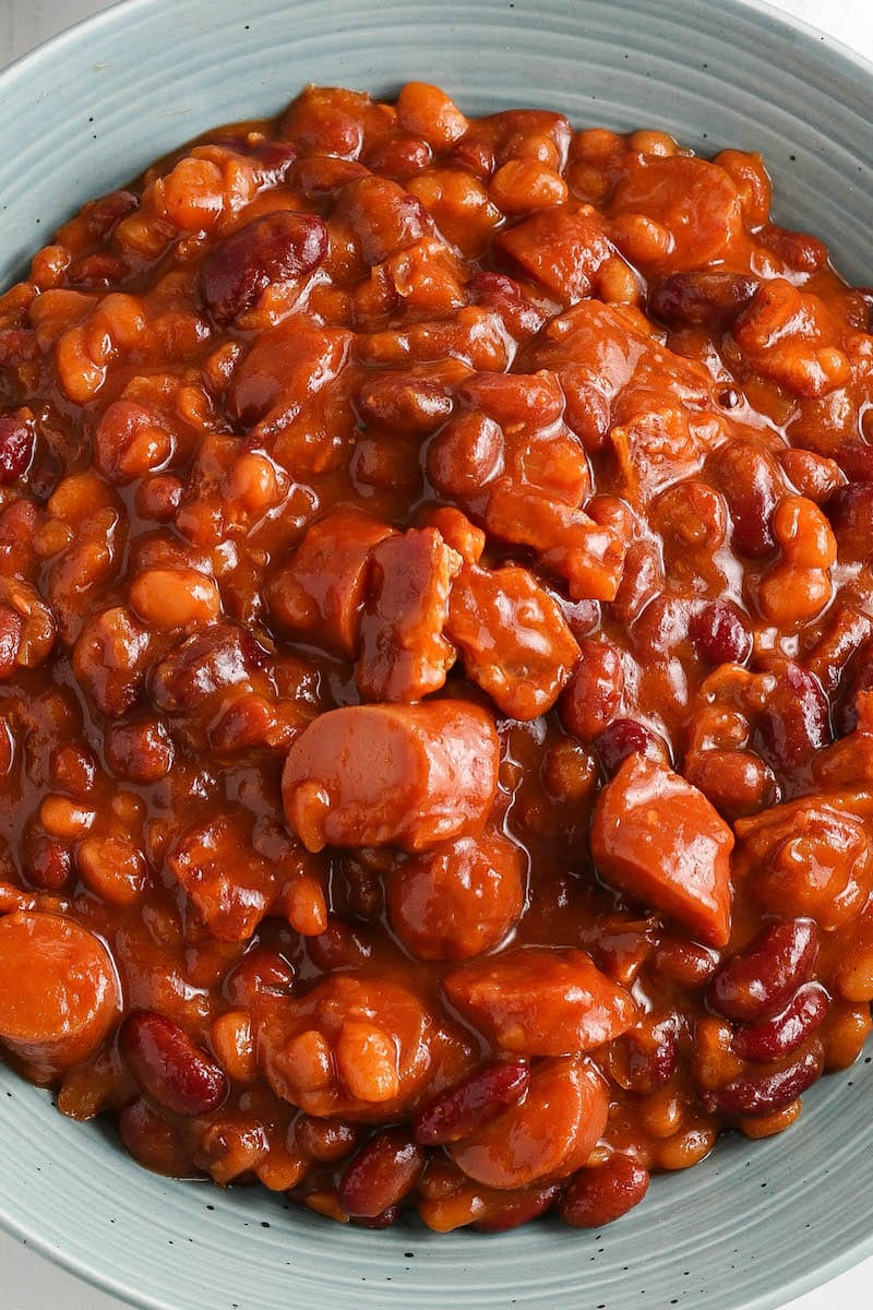 Up close image of pork and beans on a blue bowl.