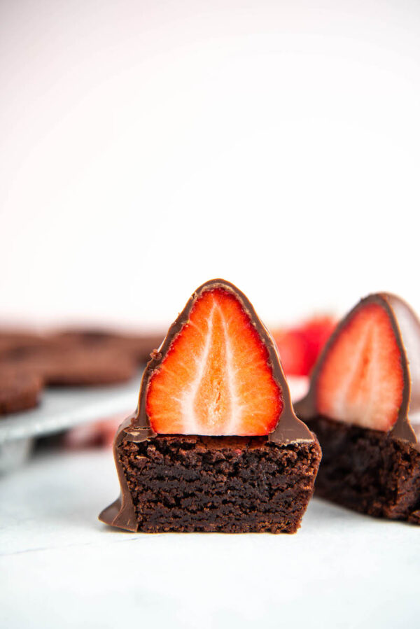 Up close image of brownies with chocolate strawberries on top.