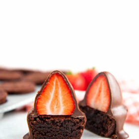 Chocolate Covered Strawberry Brownie Bites cut in half with brownie bites behind them.