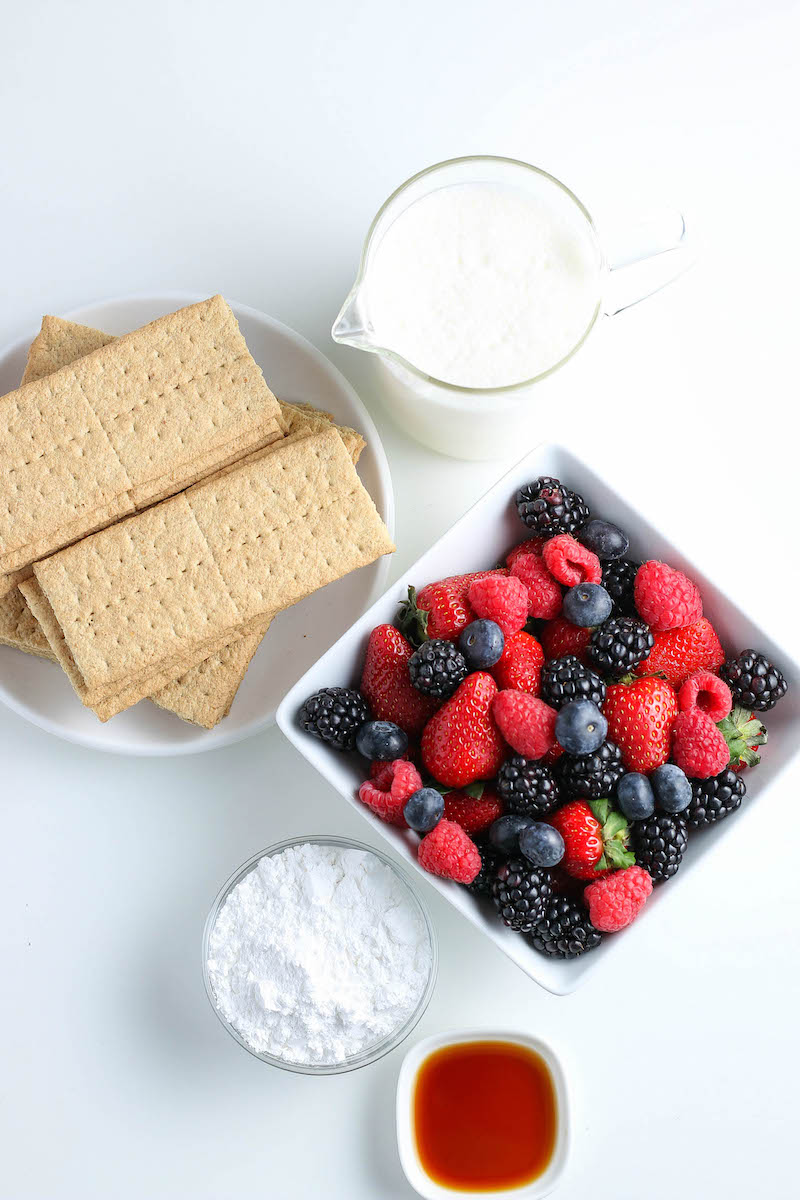 Bowl of graham crackers with a bowl of mixed berries next to it.