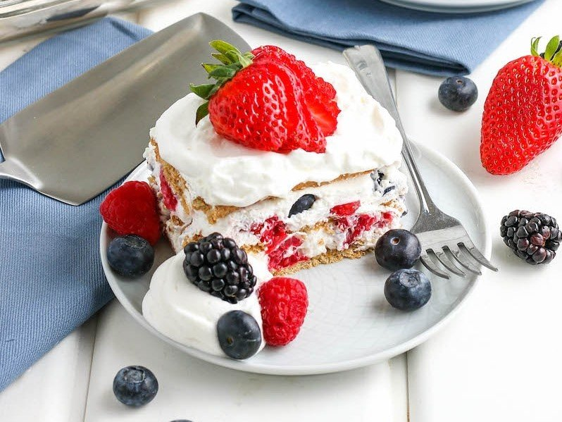A square of icebox cake with whipped cream and berries on a plate