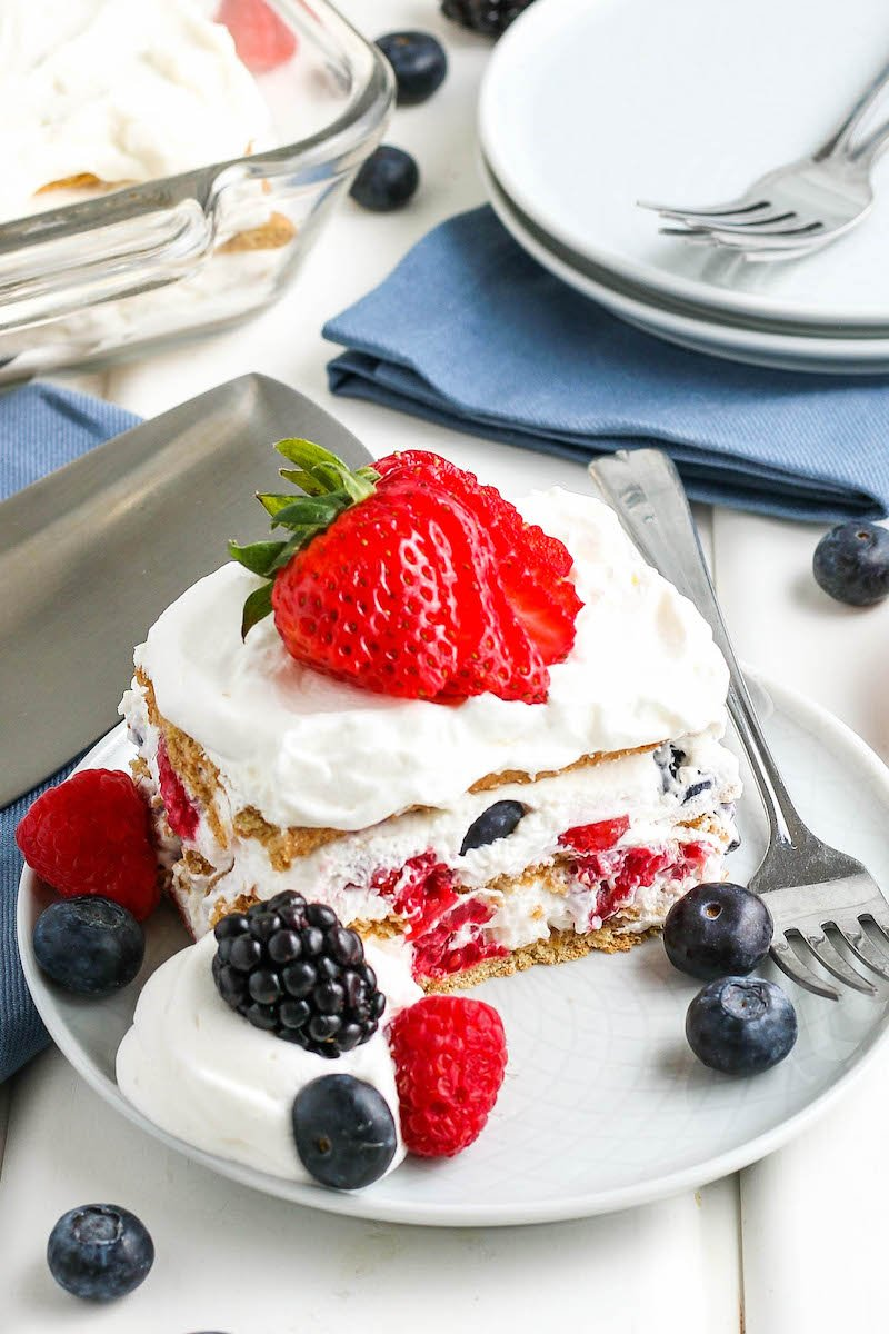 Slice of icebox cake on a plate with a sliced strawberry on top, more berries on the plate, and a fork next to it.