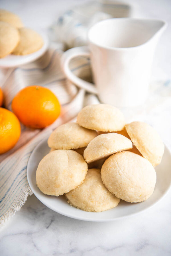 Shortbread cookies on a white plate with oranges and a pitcher of milk in the background.