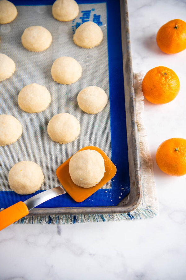Orange shortbread cookies on a cookie sheet with a spatula.