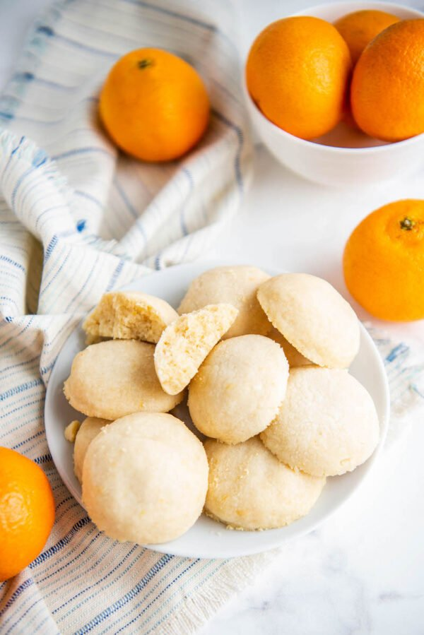 Orange whipped shortbread cookies on a white plate with one torn in half to see the inside.