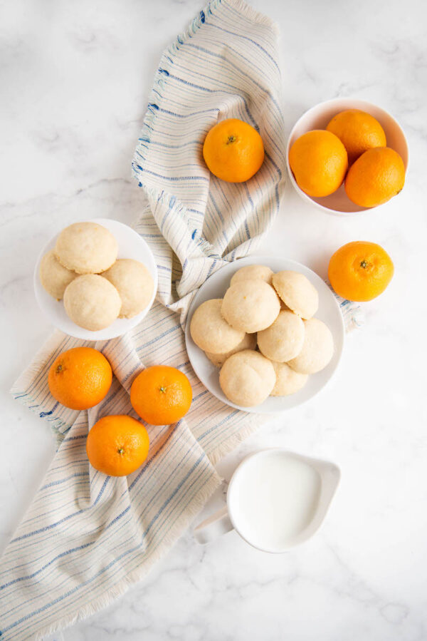 Overhead shot of whipped shortbread cookies on plates with oranges, milk and a tea towel.