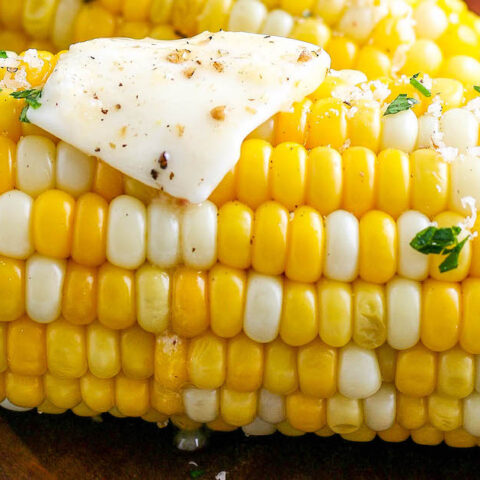 Up close image of grilled corn with butter and herbs.