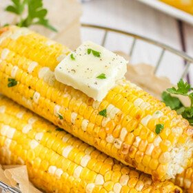 3 corn cobs with a pad of butter in a basket with parchment paper.