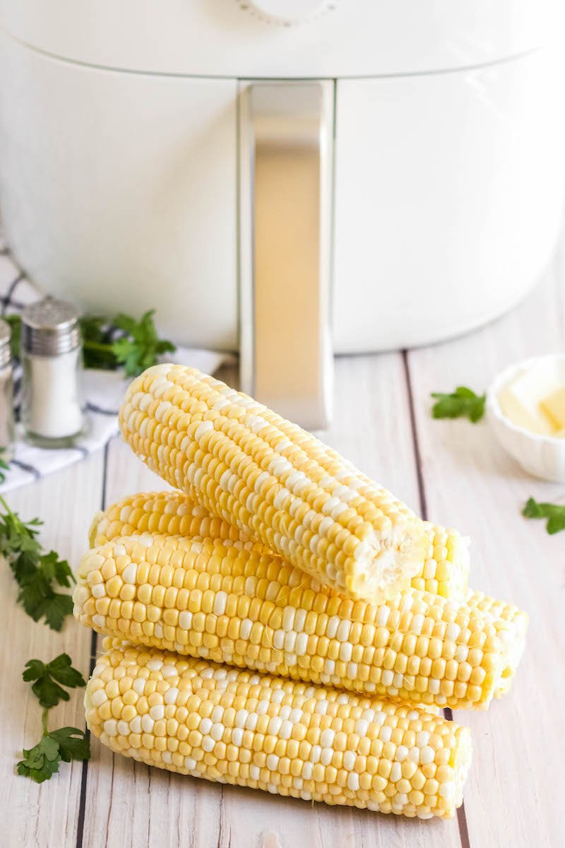 4 stacked corn cobs without seasoning on a table in front of the air fryer.