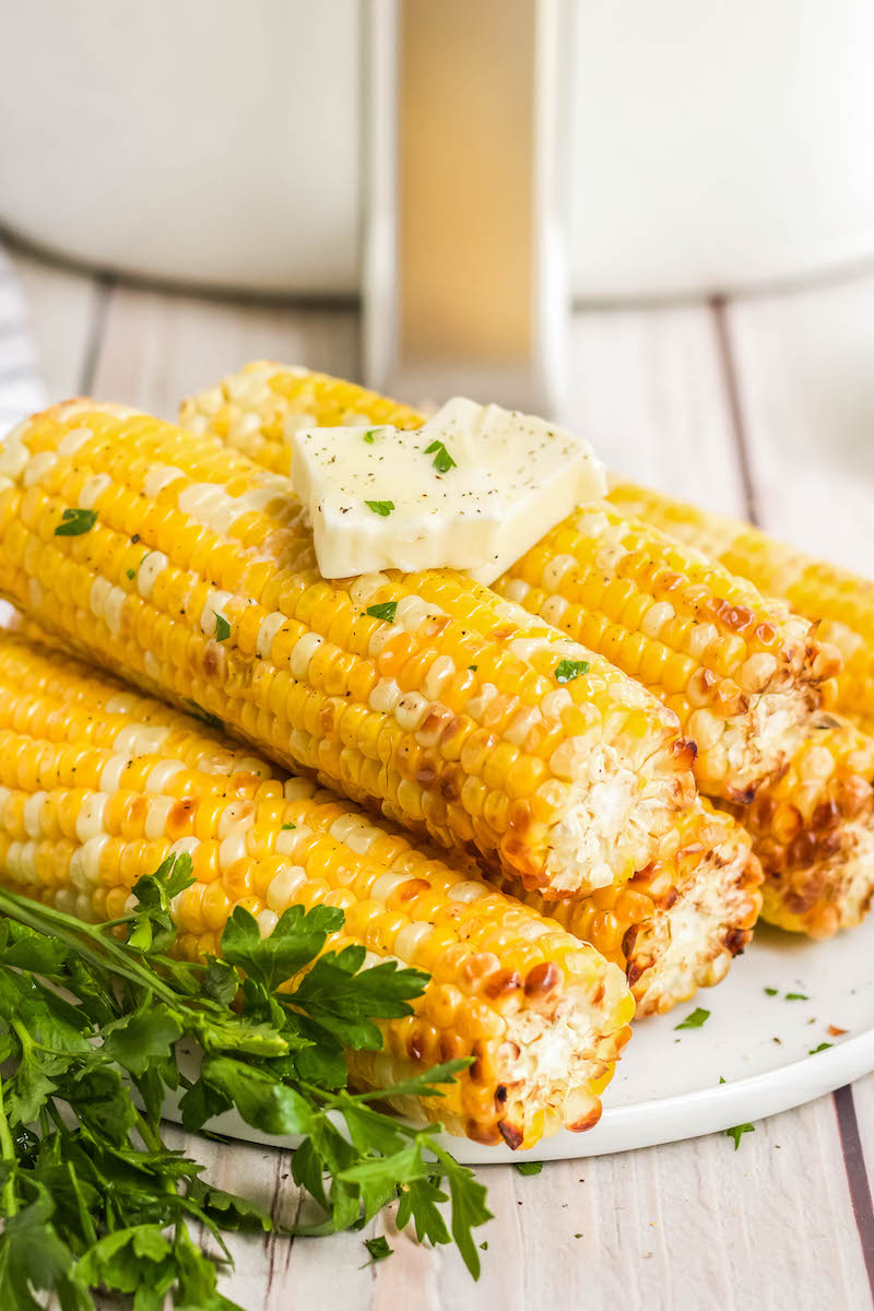 Corn cobs with 2 pads of butter on a plate next to some greens.