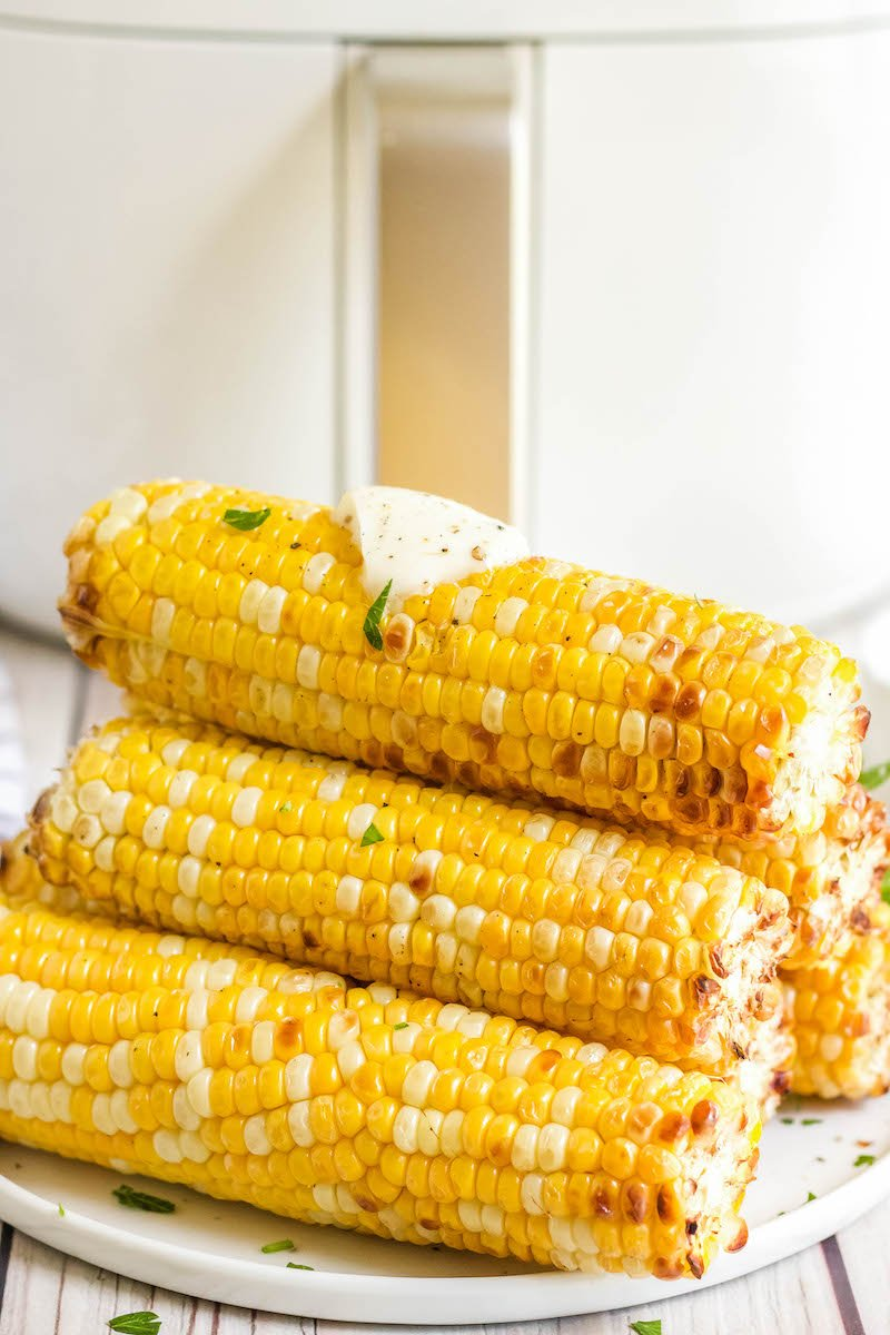 Stacked corn cobs on a plate with a pad of butter.