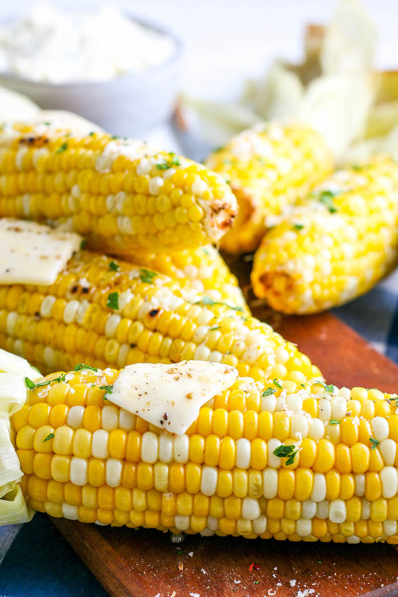 Stacked corn cobs with seasoning and butter.