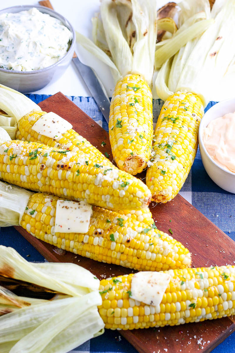 Corn cobs stacked on a wooden cutting board, seasoned and with pads of butter.