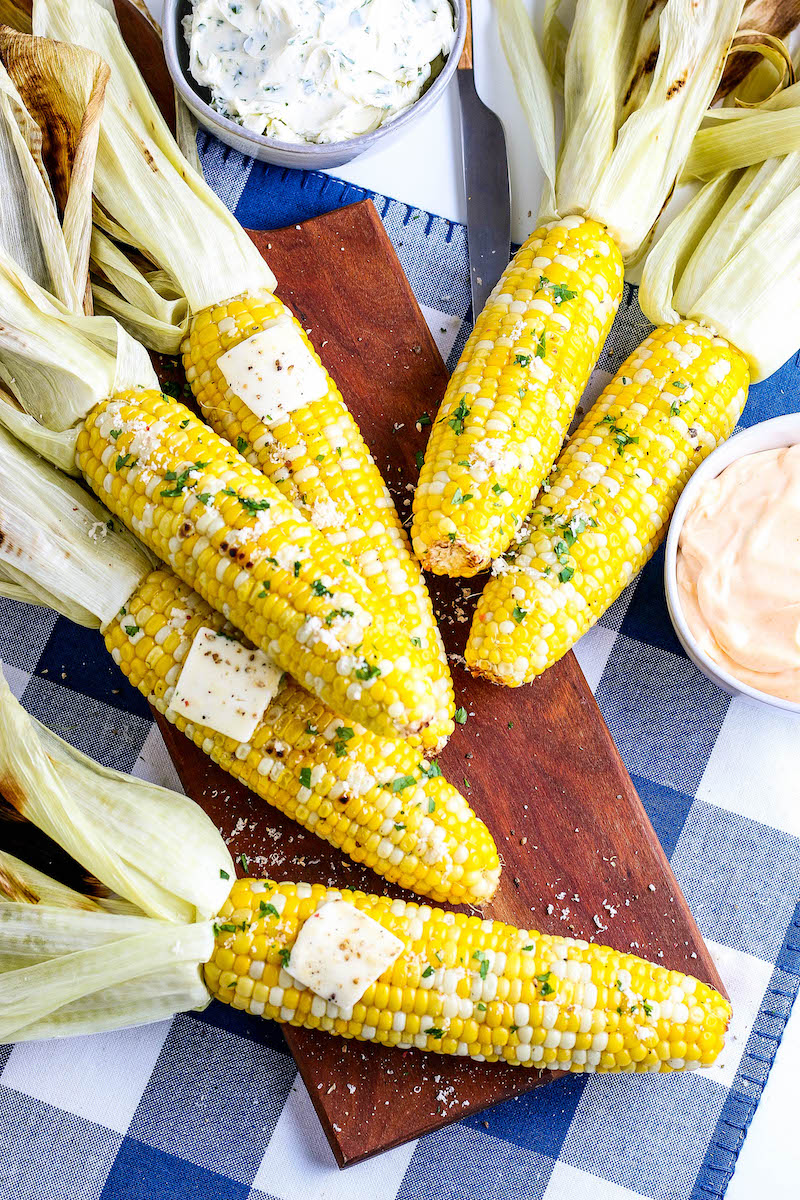 Corn cobs with husks pulled back on a wooden cutting board, with pads of butter.