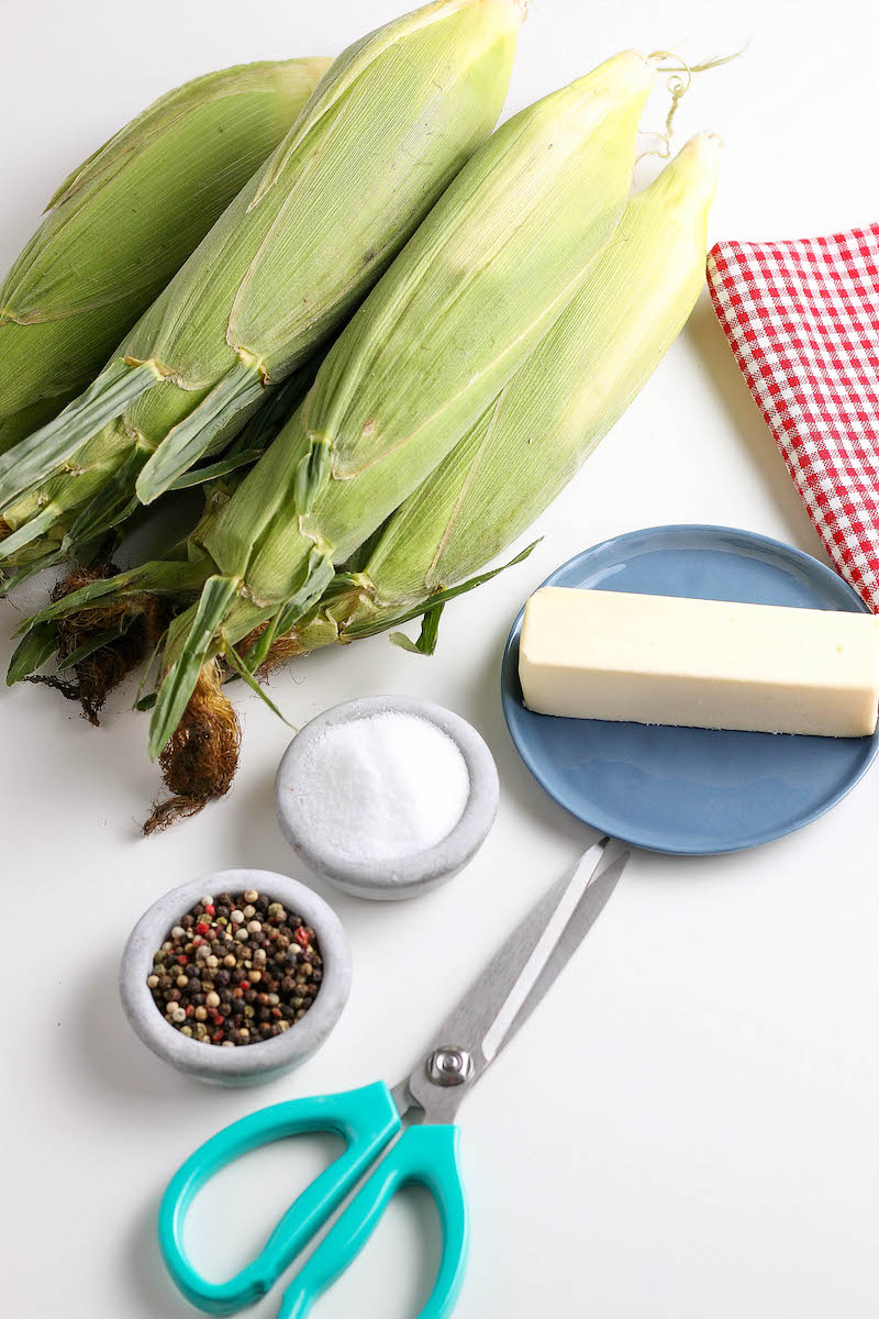 Stacked corn cobs in their husks with bowls of salt and freshly stacked pepper, next to a stick of butter and scissors.