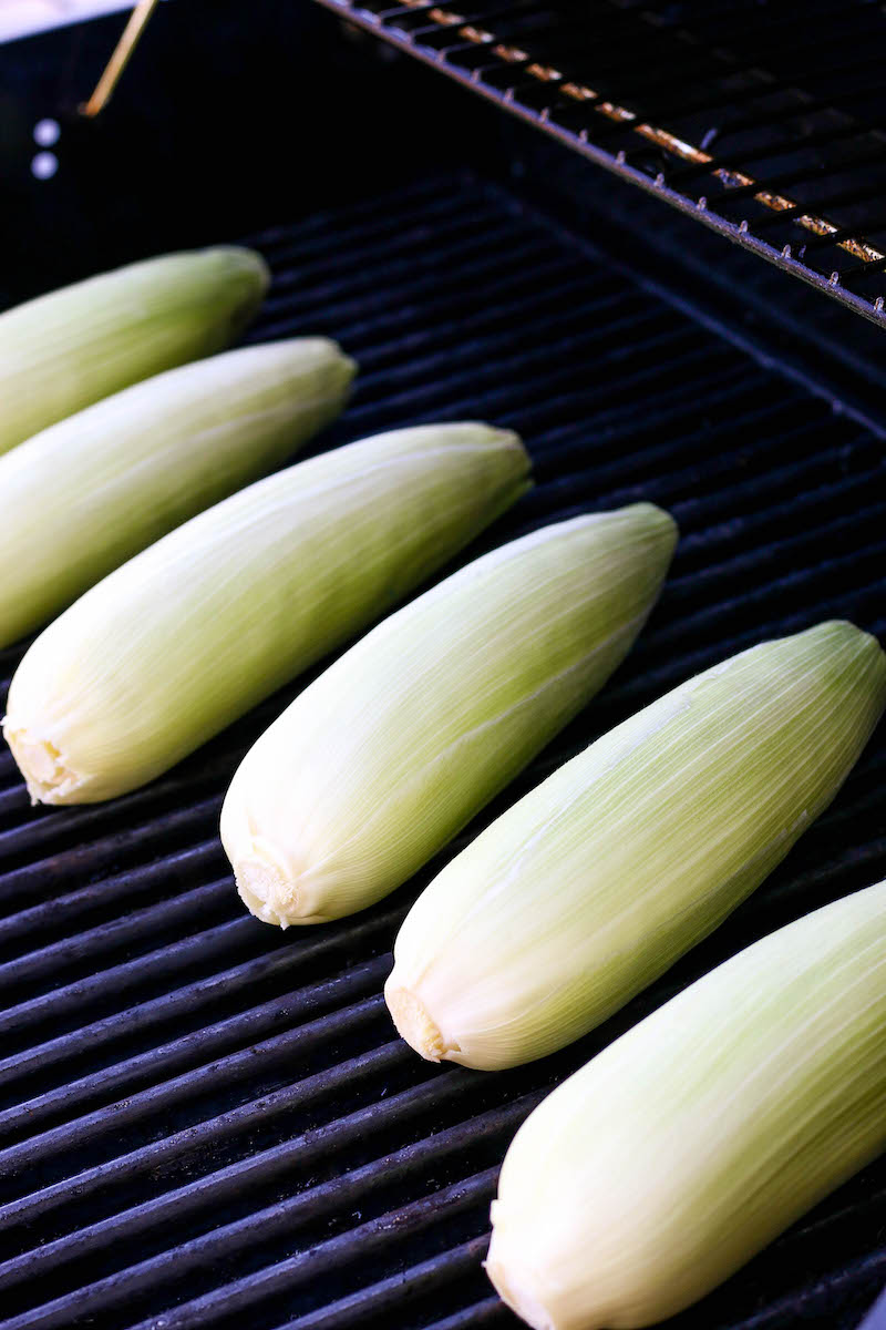 Corn cobs in a row on the grill.