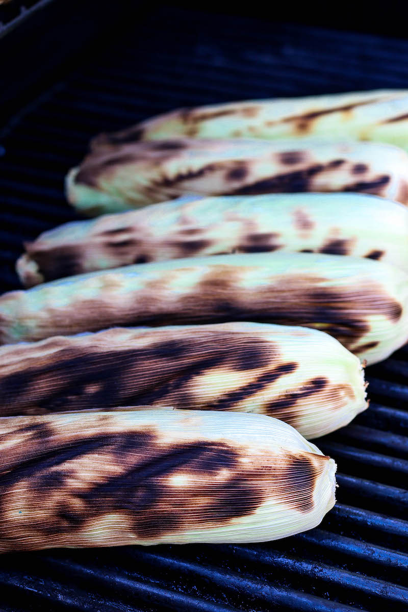 Corn cobs in a row on the grill with char marks.