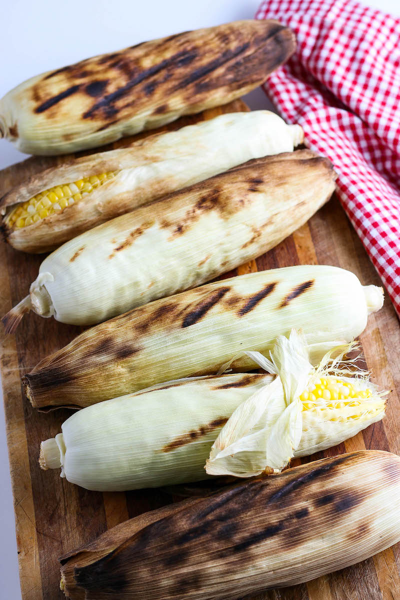 Corn cobs on a wooden cutting board with char marks, partly peeled.