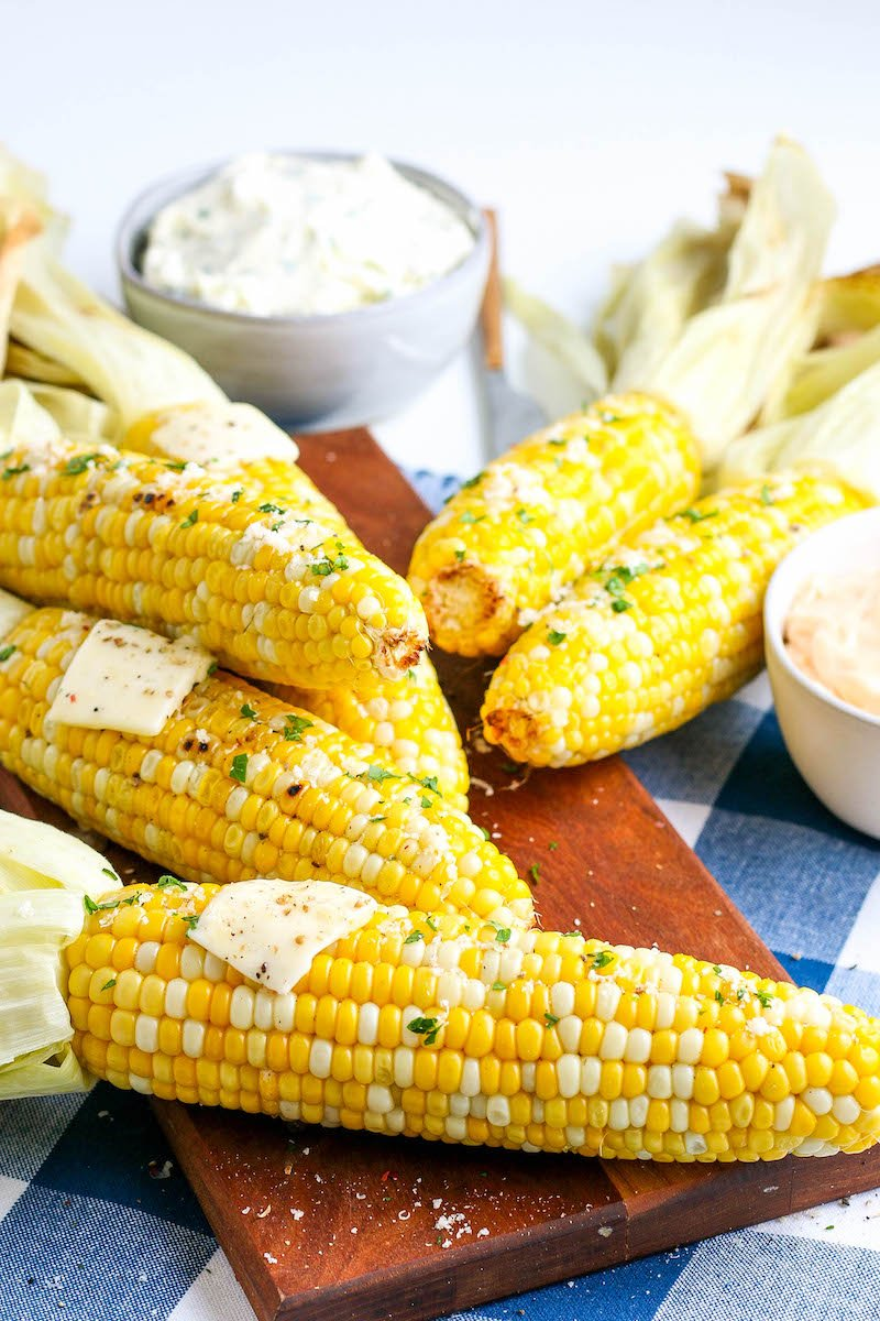 Corn cobs with the husks peeled back with pads of butter, on a wooden cutting board.