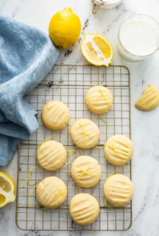 Overhead view of whipped shortbread cookies on a cookie sheet with a tea towel and lemons.