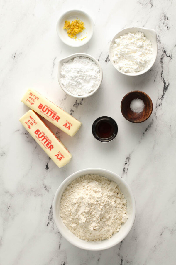 Ingredients for shortbread cookies in bowls on a marble countertop.