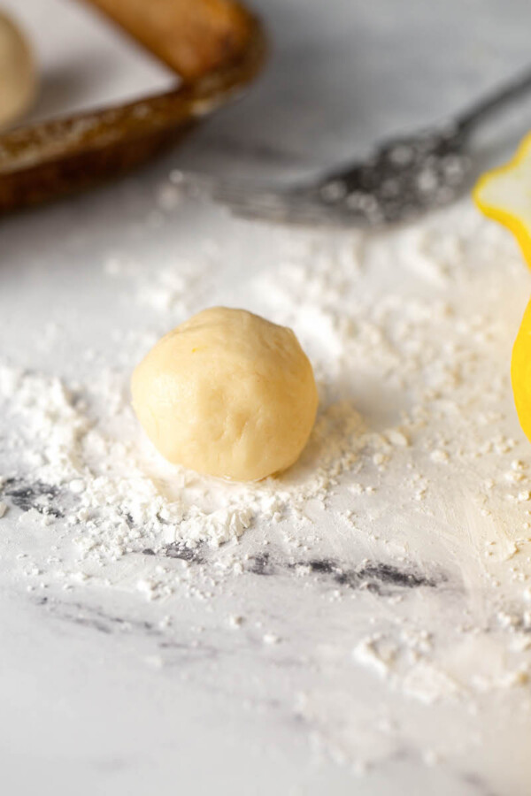 Shortbread cookie dough balls with cornstarch on a marble countertop.