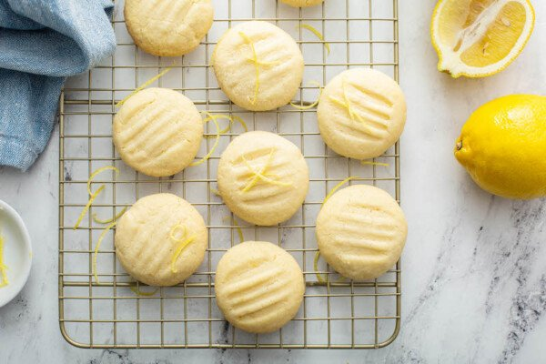 Overhead image of lemon whipped shortbread cookies on a cookie sheet with lemons and a blue tea towel.