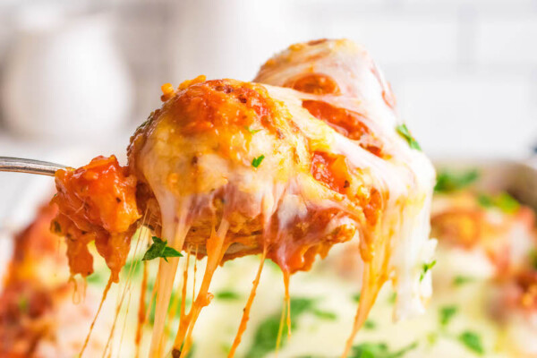 Up close image of Meatball Sub Casserole with pulled cheese on a spoon.