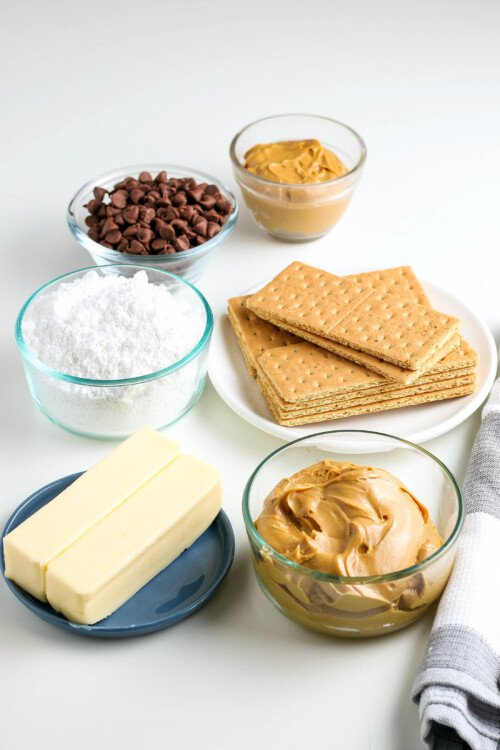 A plate with two sticks of butter, a big bowl of peanut butter, a small bowl of peanut butter, a bowl of chocolate chips, a bowl of powdered sugar, and a bowl of graham crackers.