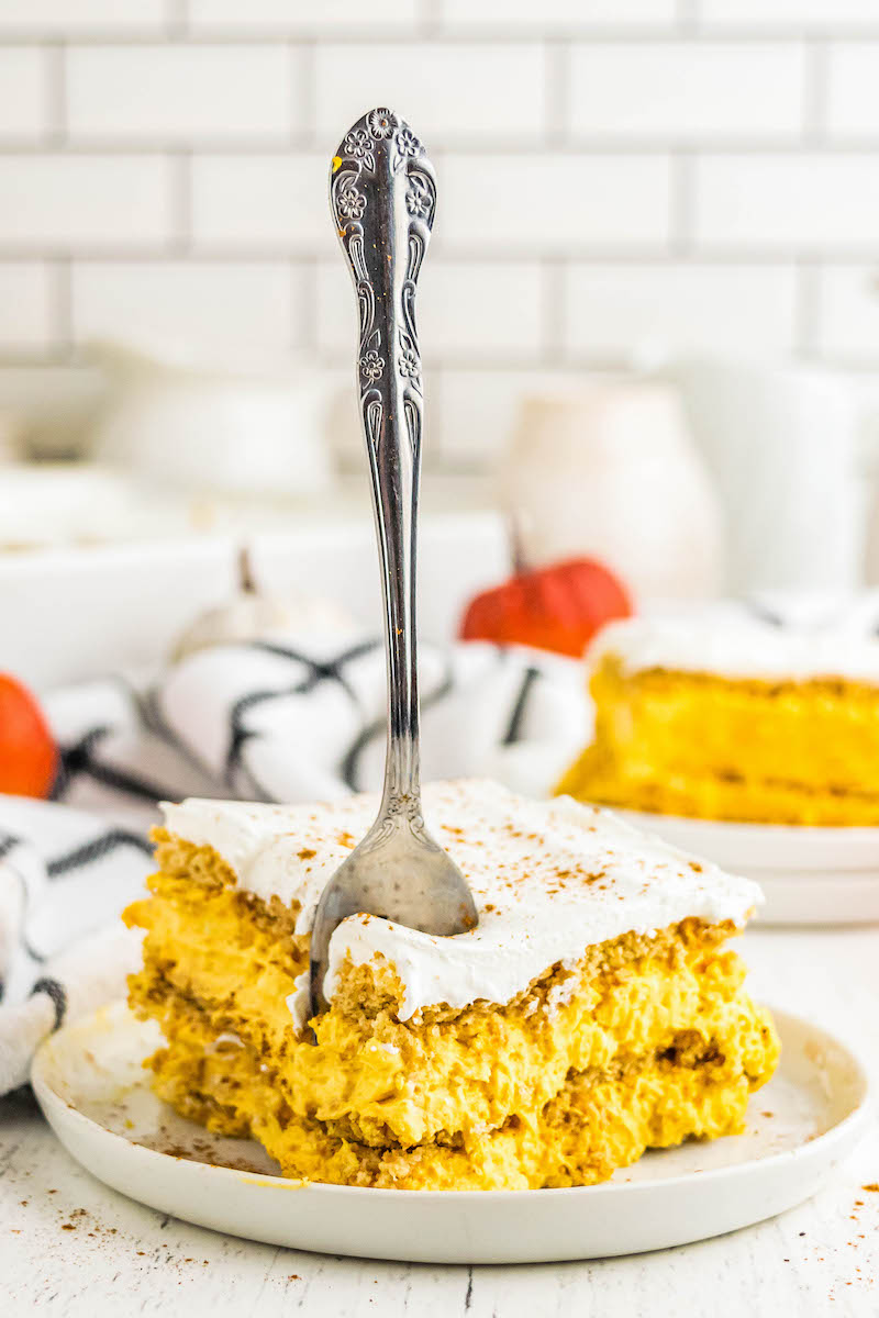 Slice of pumpkin ice box cake on a plate, with a fork in it.