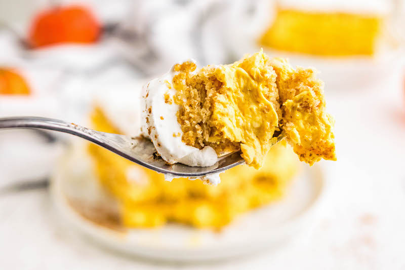 Fork full of pumpkin ice box cake with a cool whip topping.