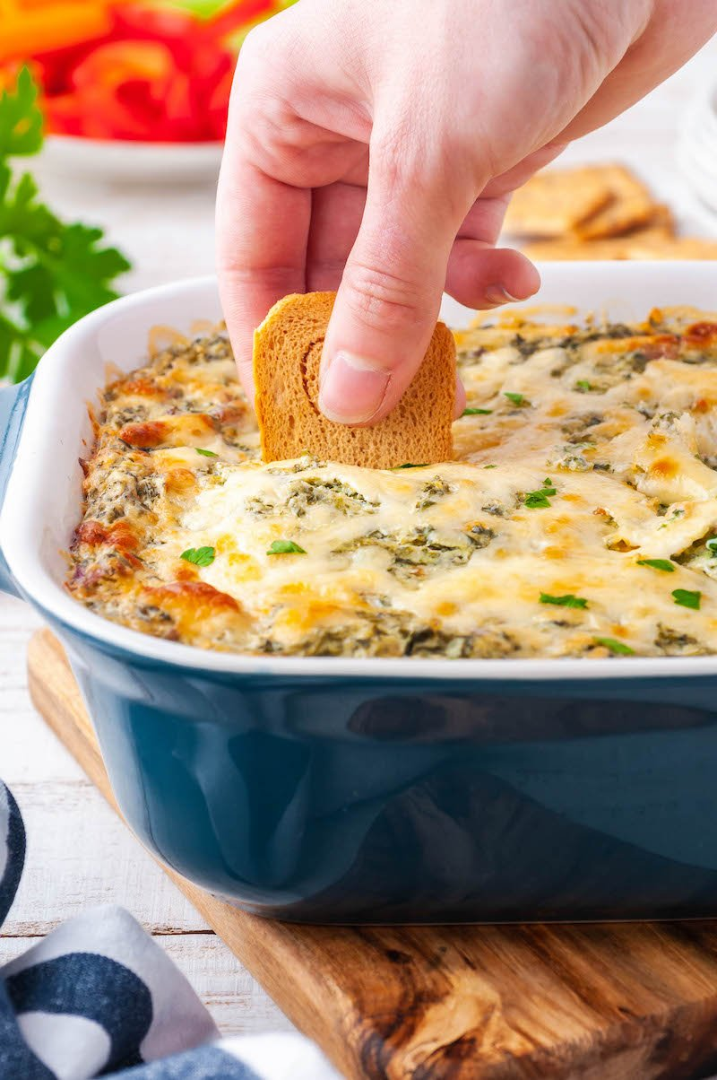 Baked spinach dip in a pan with a cracker in it.