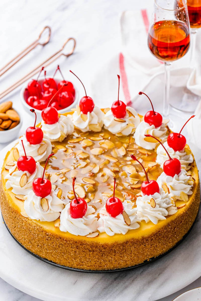 Almond amaretto cheesecake with whipped cream and maraschino cherries.