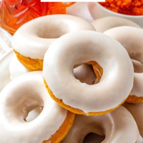 Pumpkin donuts stacked on top of each other on a white plate.