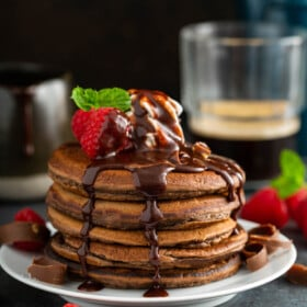 Chocolate pancakes stacked on a white plate with chocolate sauce and raspberries on top.