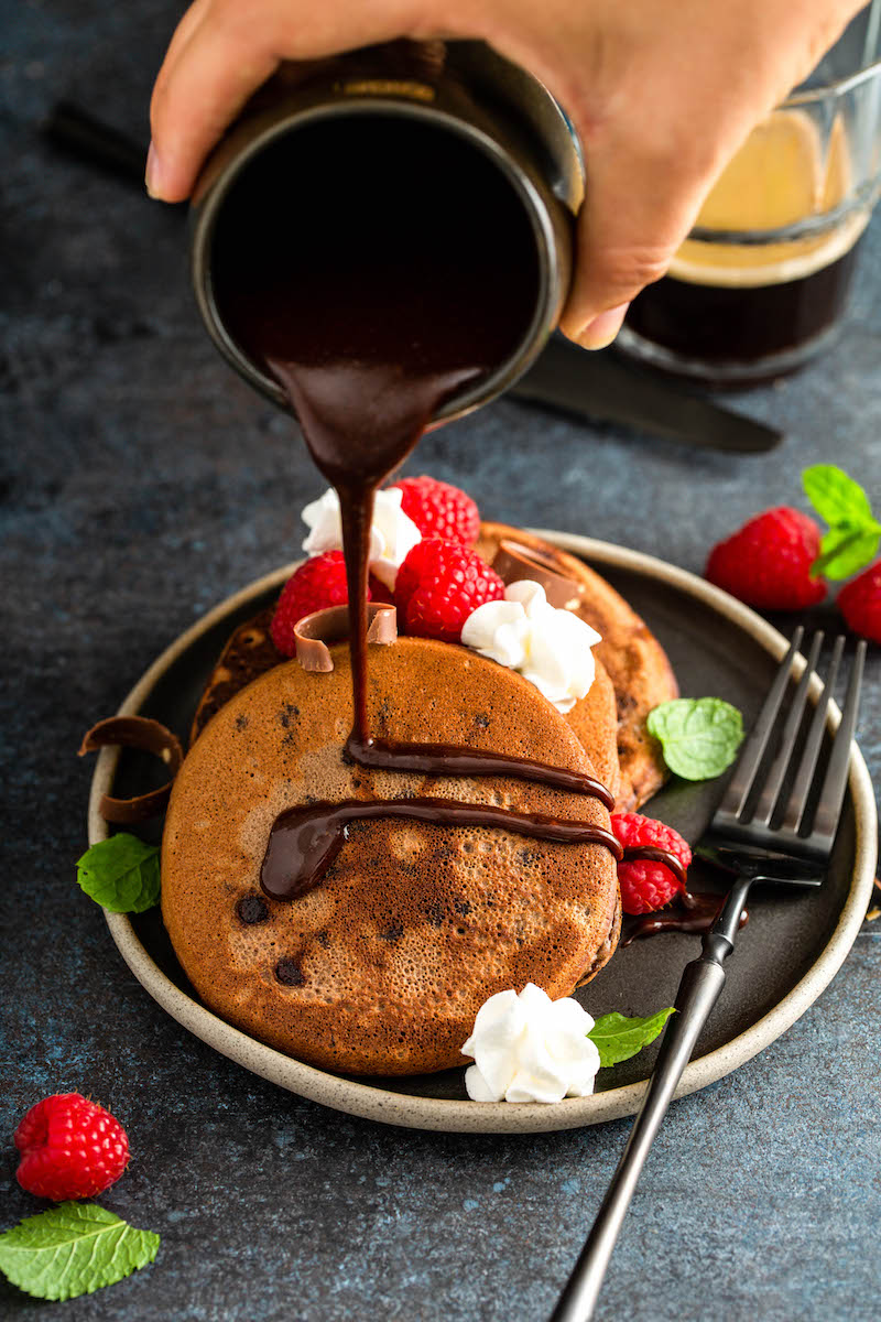 Chocolate sauce being drizzled over pancakes on a plate.
