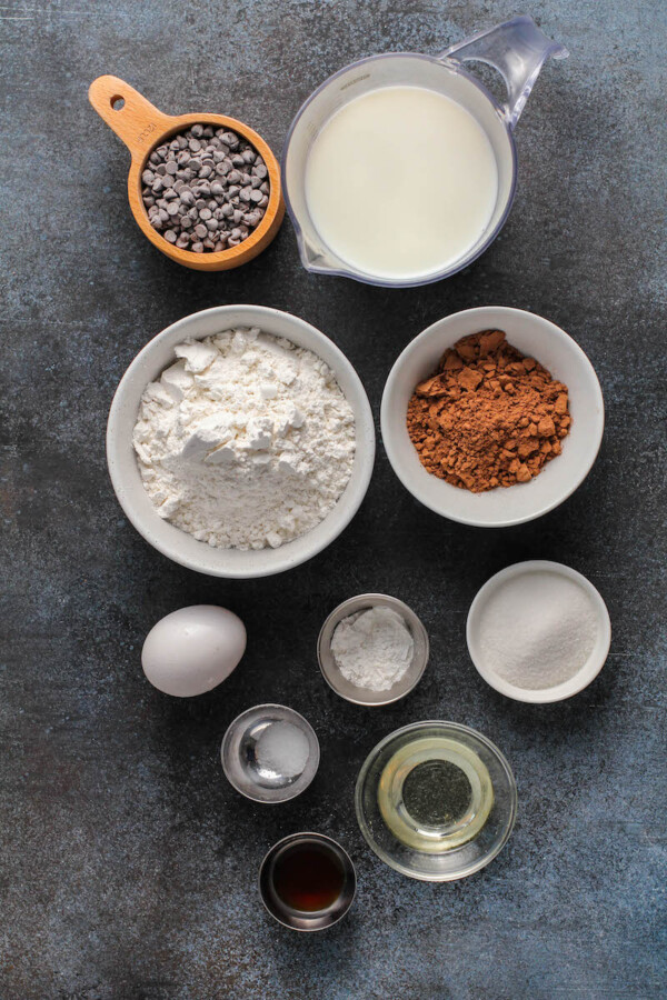 Overhead view of pancake ingredients in bowls on a dark board.