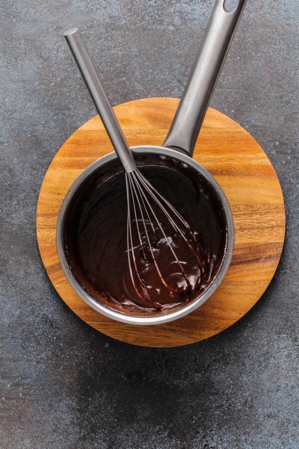 Chocolate sauce in a sauce pan with a whisk inside on a wood cutting board.