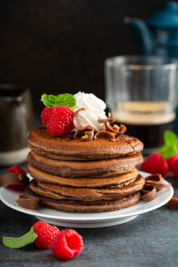 Fluffy chocolate pancakes on a white plate with whip cream and raspberries on top and on the side.