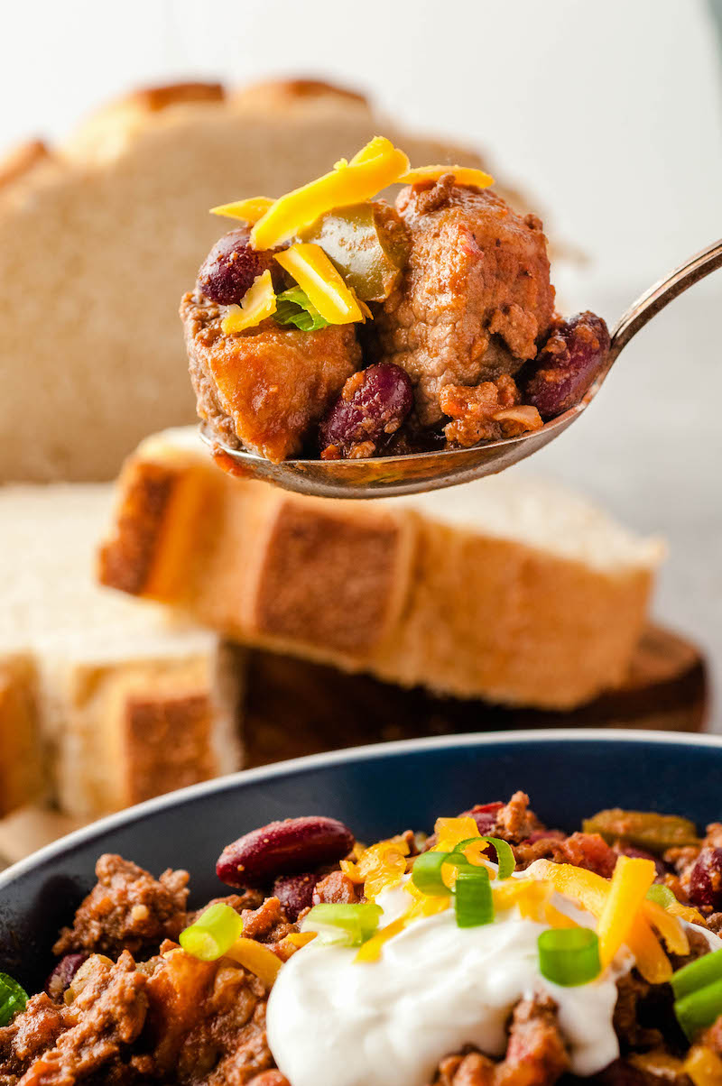 Spoonful of chunky chili with cheese.