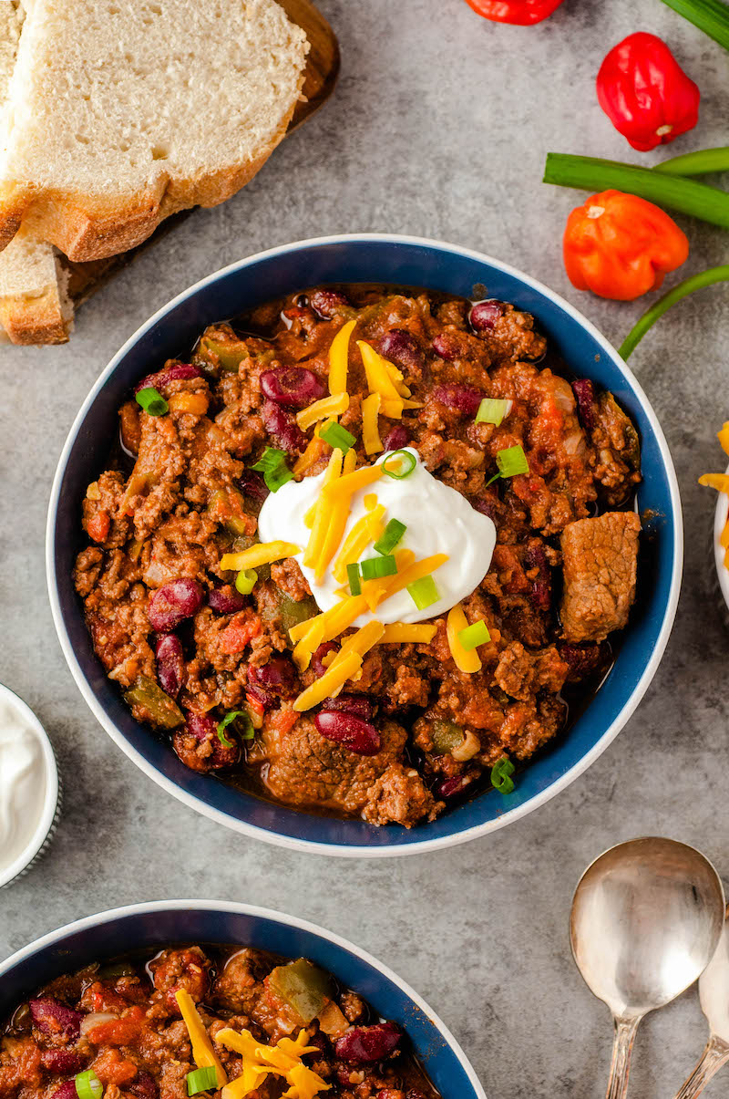 Bowl of chunky chili with cheese and sour cream.