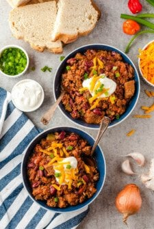Two bowls of chili with cheese and sour cream on top.