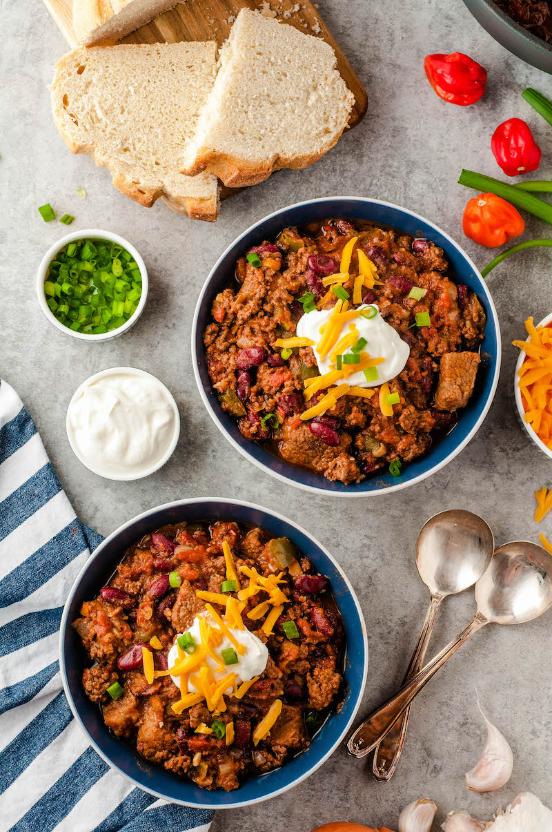 Two bowls of chili with cheese and sour cream.