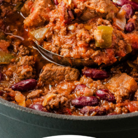Chili in a pot with a ladle scooping up some.
