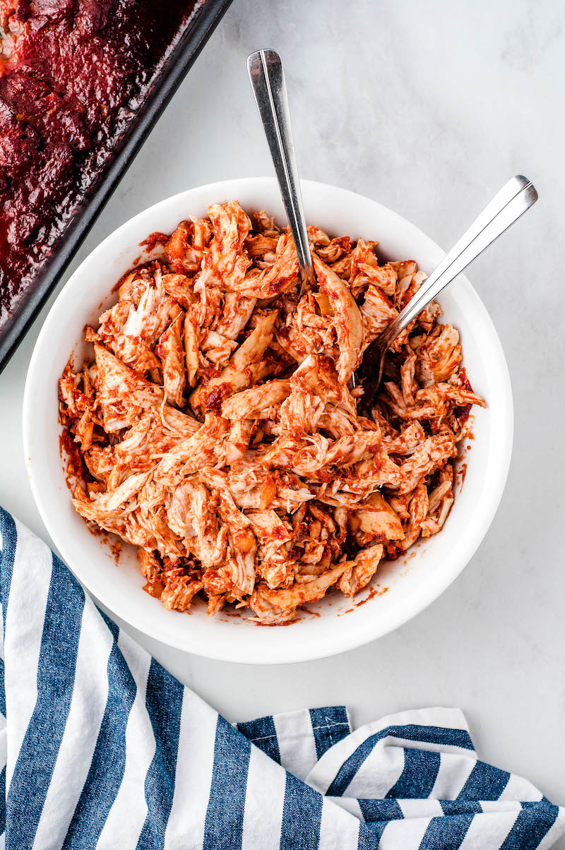 Pulled chicken in a bowl with two forks.