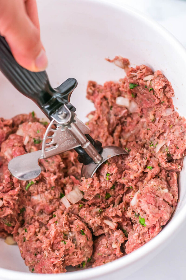 Ground beef meatball mixture being mixed together.