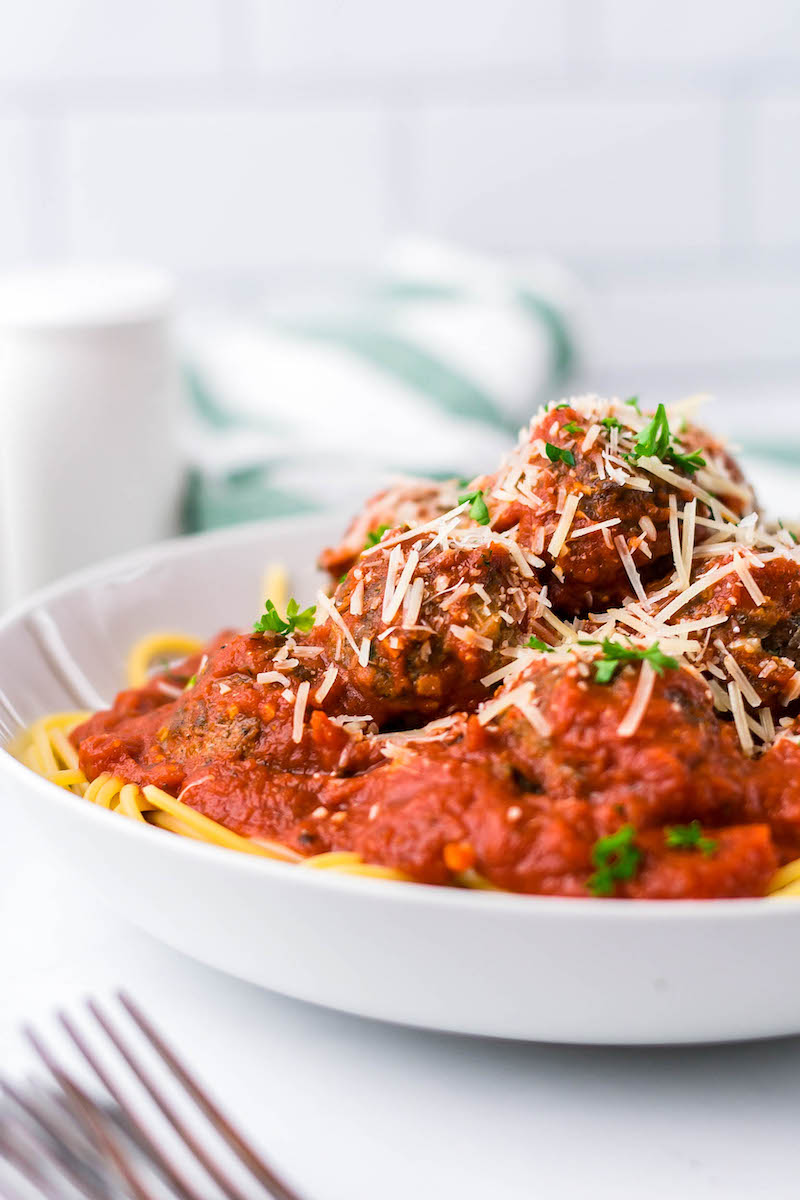 Bowl of meatballs over pasta with tomato sauce.