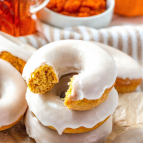 Stacked maple glazed pumpkin donut with a bite taken out of it.