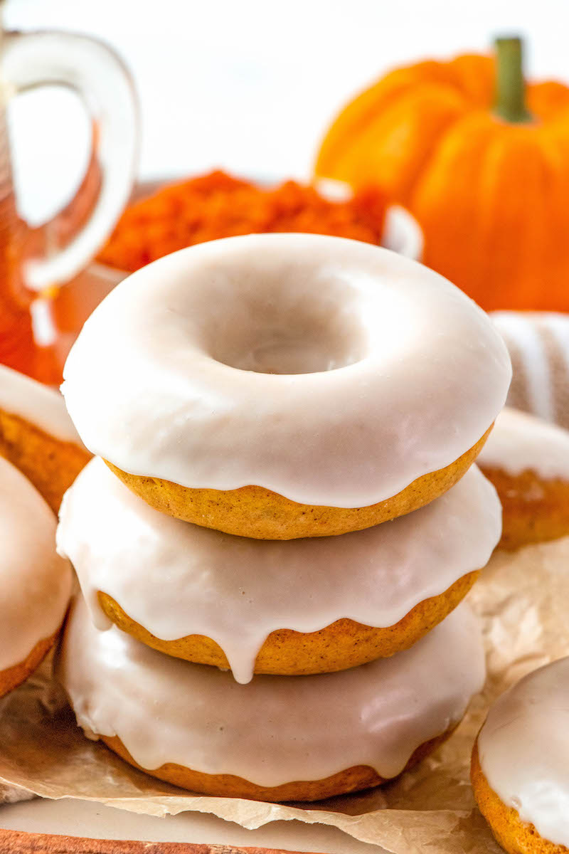 Three stacked pumpkin donuts with maple glaze.